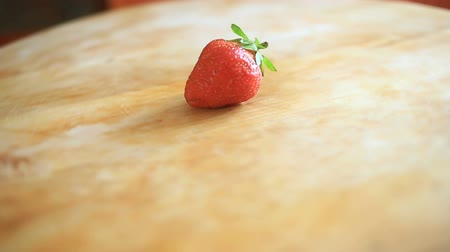 mono : One strawberry berry lies on a wooden board that rotates around its axis
