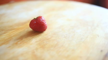 juicy : One strawberry berry lies on a wooden board that rotates around its axis