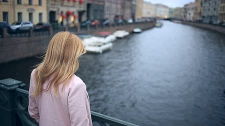 bab : A woman in a coat stands on a bridge and looks down at the black water.