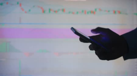 bonds : Hand of the person with the phone, typing a text message on the smartphone on the background of the LCD screen with the graph, financial market exchange - graph.