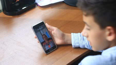 conferencing : Boy teenager holds a video chat with a woman on a smartphone