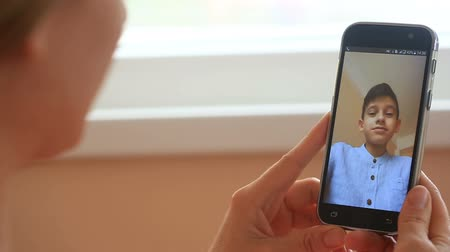 conferencing : A woman is conducting videochat on a smartphone with a child Stock Footage