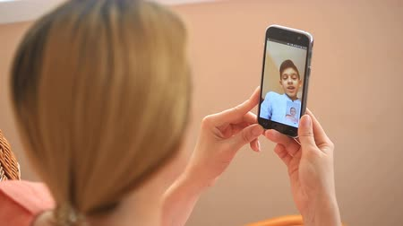 в середине : A woman is conducting videochat on a smartphone with a child Стоковые видеозаписи