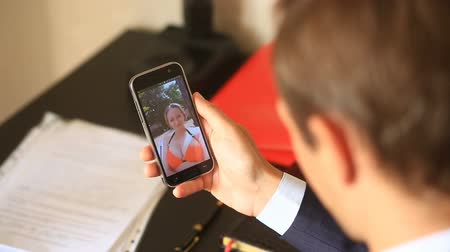 болваны : A businessman in a suit, sitting in the office at his desk, holds a video chat with a girl on the beach. She is dressed in a swimsuit and invites him to join her