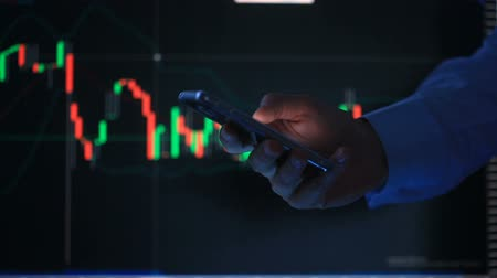 tárcsázás : Hand of the person with the phone, typing a text message on the smartphone on the background of the LCD screen with the graph, financial market exchange - graph.