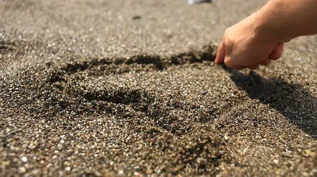 alegori : The hand paints the heart on the brown sand