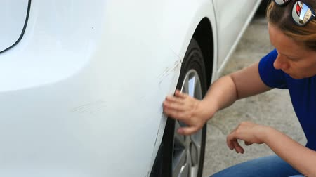 fender : looking at a damaged vehicle. Woman blonde inspects car damage after an accident
