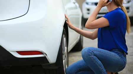 vrak : looking at a damaged vehicle. Woman blonde inspects car damage after an accident