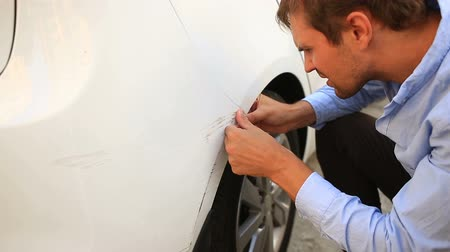 fender : looking at a damaged vehicle. man inspects car damage after an accident