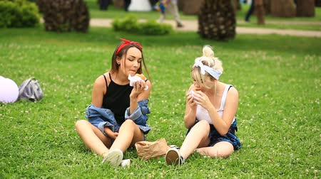 stroll : Two girlfriends eat hamburgers, french fries on a green lawn in the city garden. fast food Stock Footage