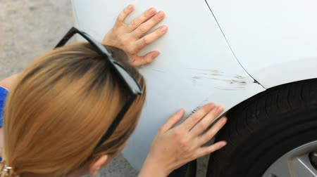 carelessness : looking at a damaged vehicle. Woman blonde inspects car damage after an accident