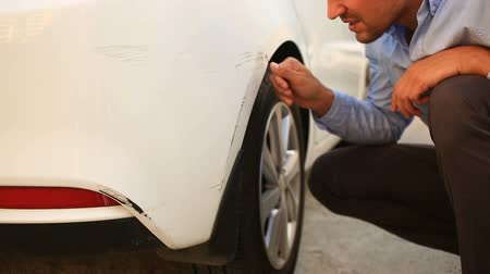 smashing : looking at a damaged vehicle. man inspects car damage after an accident