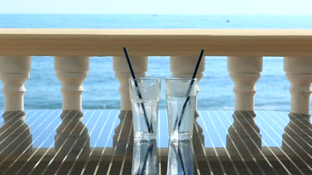 perspiration : Two glasses of water with ice on the restaurant table overlooking the sea. Against the background of sea waves. copy space.