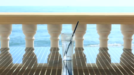 perspiration : glass of water with ice on the restaurant table overlooking the sea. Against the background of sea waves. copy space. Stock Footage