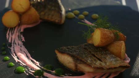 pasztet : A dish of haute cuisine. close-up. Fish with young potatoes. mullet. With a glass of white wine. Primorsik restaurant with a view to the sea.