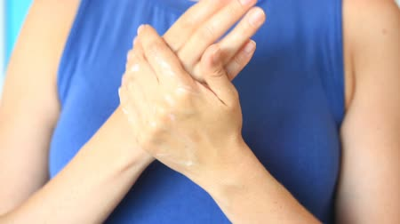 seio : woman is creaming her hands for soft skincare. A woman smears her hands with a hand cream on the background of her breast. Stock Footage