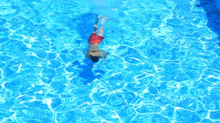 plavec : The child is swimming in the blue water of the pool. view from above. The boy dives under the water in the pool