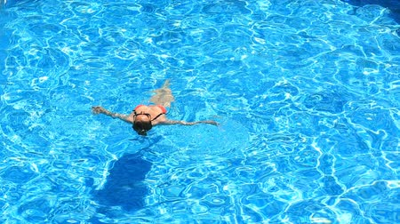 болваны : Blond pretty woman enjoying the water in the pool. View from above