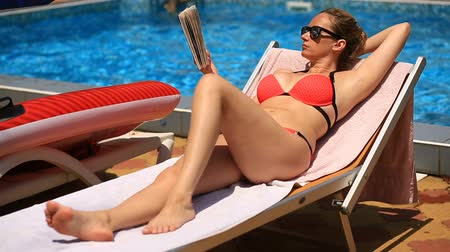 literary : Young, elegant woman reading book on sunbed by pool