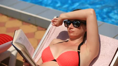 edebi : Young, elegant woman reading book on sunbed by pool