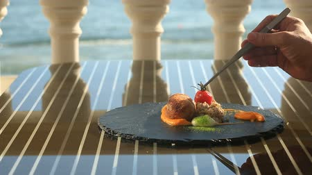 seafood dishes : The chief cook decorates a dish of high cuisine with the help of tongs. Dishes at the gourmet restaurant. Close-up. Cutlet from rabbit meat with a garnish of green buckwheat