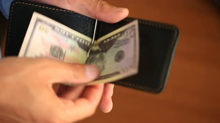 казна : Mens hands hold a money clip with dollars