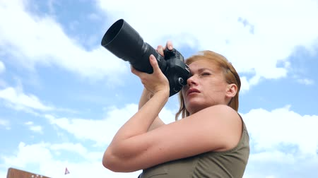 professional photography : A close-up of a female photographer is taking pictures in the street with the help of a professional camera. 4k, slow motion