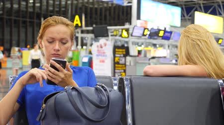 emocional : Woman uses a smartphone in airport waiting lounge. Expectations of flight at airport. 4k, slow motion Stock Footage