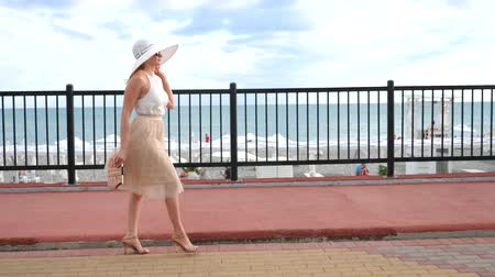 debriyaj : An elegant woman in a hat and a white air dress strolls along the waterfront. General shooting. 4k, slow-motion