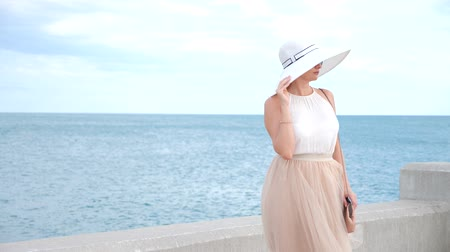 rejoice : An elegant woman in a white broad-brimmed hat and sunglasses enjoys the sea view. 4k, slow-motion