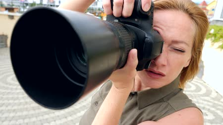 viewfinder : A close-up of a female photographer is taking pictures in the street with the help of a professional camera. 4k, slow motion