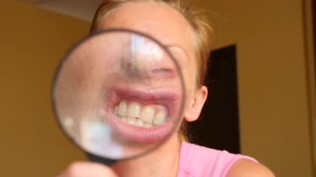 növelni : The woman without make-up with a magnifier in a hand. 4k, slow-motion