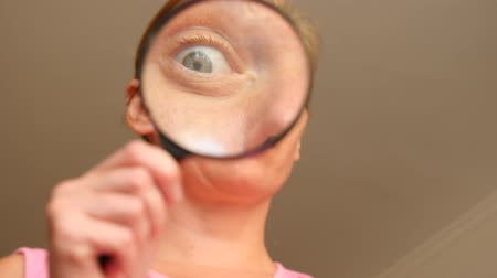 without face : The woman without make-up with a magnifier in a hand. 4k, slow-motion