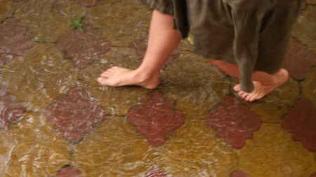 sandals : Bare feet splash through puddles pooled on red pavers during a rainstorm, slowed motion. 4k