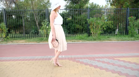 handbag : An elegant woman in a hat and a white air dress strolls along the waterfront. General shooting. 4k, slow-motion