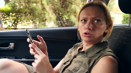 dark eyes : A woman is driving in the car next to the driver and is talking on the phone. 4k, slow-motion Stock Footage
