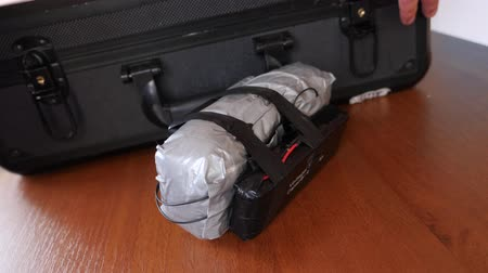 biztosíték : A man puts a homemade explosive device in his suitcase. Preparation of terrorist act. 4k. Slow motion