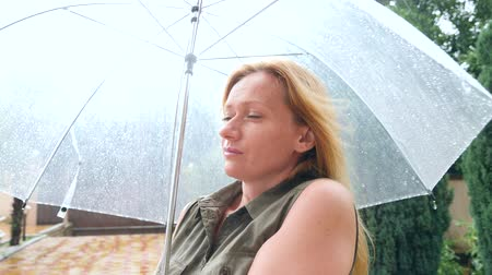 into the camera : A woman is standing under an umbrella. Summer torrential downpour. 4k, slow-motion