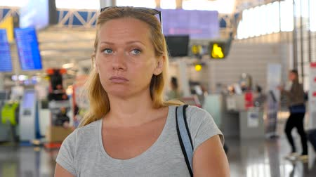 fáradt : Woman in airport waiting lounge. Expectations of flight at airport. 4k, slow motion, The girl at the airport looks at the information board.