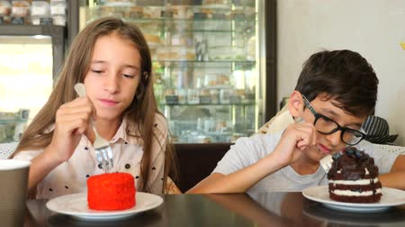 souffle : children, brother and sister, twins eat a delicious dessert in a cafe. 4k slow motion Stock Footage