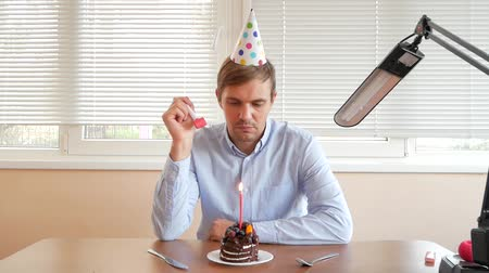 newyear : a lone man celebrates a holiday, he sits alone at a table with a cake and a candle. Stock Footage