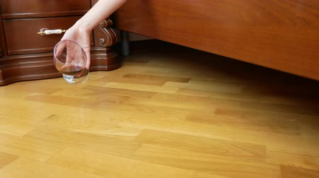 alkoholismus : close-up, female hand dropping a glass of red wine from the bed. the remnants of wine are poured onto the floor. slow motion 4k