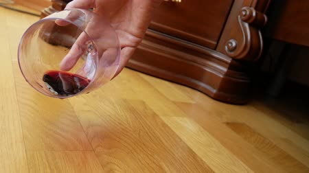geçti : close-up, female hand dropping a glass of red wine from the bed. the remnants of wine are poured onto the floor. slow motion 4k