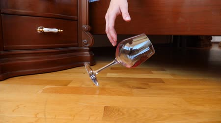 red wine : close-up, female hand dropping a glass of red wine from the bed. the remnants of wine are poured onto the floor. slow motion