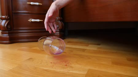 geçti : close-up, female hand dropping a glass of red wine from the bed. the remnants of wine are poured onto the floor. slow motion