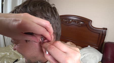 earlobe : womens hands cleans the ear of a man. with a cotton swab, personal hygiene. 4k, action
