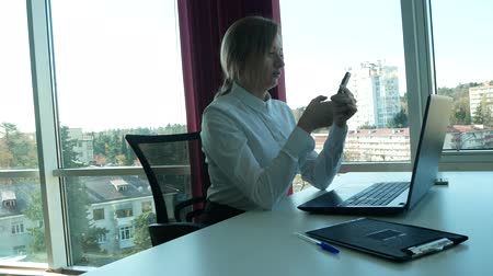 secretário : business woman in a modern office with a panoramic window, sunny day, laptop, tablet, use a mobile phone in a situation. 4k, slow motion Vídeos