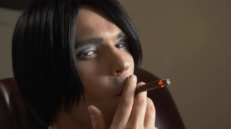 peruca : a young man in the image of a transsexual seductively smoking a cigar in the twilight and releasing smoke into the camera. 4k, slow motion