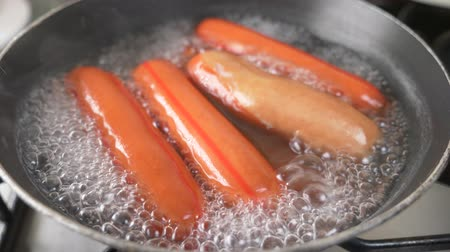 colesterol : uncooked sausages are boiled in water on a gas stove. 4k, slow motion