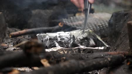 temperada : 4k, slow motion. a man-tourist shoots a fire for a grill in the forest.